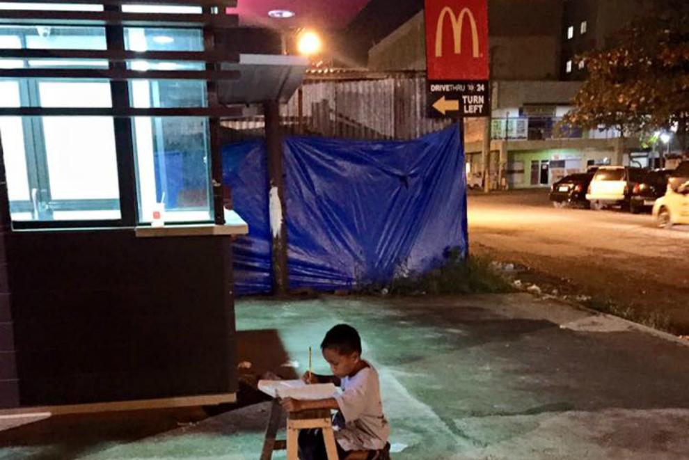 Straßenkind lernt nachts im Licht von McDonald's