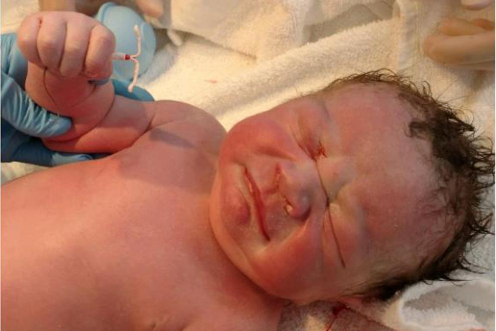 Neugeborenes Baby hält Spirale seiner Mutter in der Hand